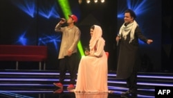 Afghan singer Zulala Hashemi (center) performs alongside competitors Sayed Jamal Mubarez (left) and Babak Mohammadi during the television music competition Afghan Star on March 9.