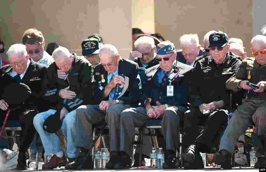 American veterans observe a minute of silence during a joint U.S.-French D-Day commemoration ceremony at the Normandy American Cemetery and Memorial in Colleville-sur-mer.