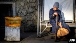 Пожилая женщина сидит на трамвайной остановке. Краснодар, 13 ноября 2017 года.