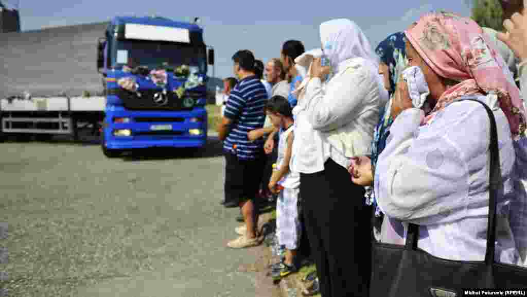 Bosnians watch as one of the trucks carrying some of the Srebrenica victims arrives in Potocari, where they will be buried, on July 9.