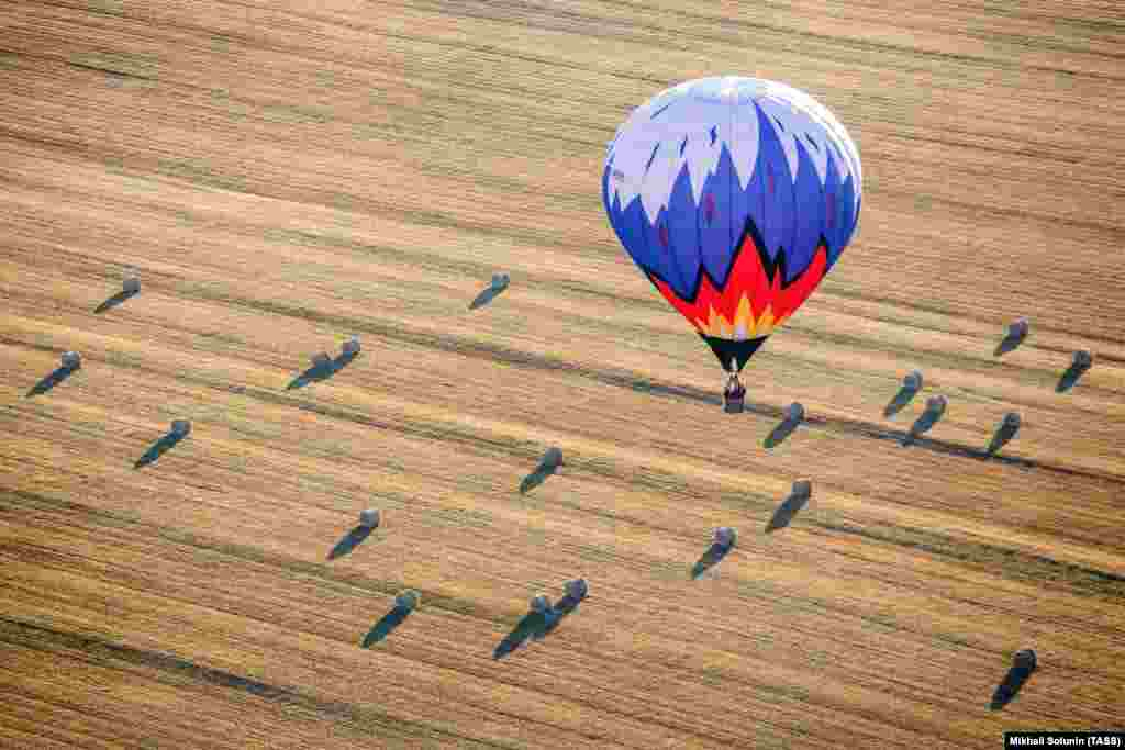 A hot-air balloon flies over a field during the Russian Volga Federal District hot-air balloon championships. (TASS/Mikhail Solunin)