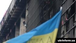 Робітник комунальних служб обрізає частини металевого каркасу залізобетонної конструкції Будинку профспілок, Київ, 1 квітня