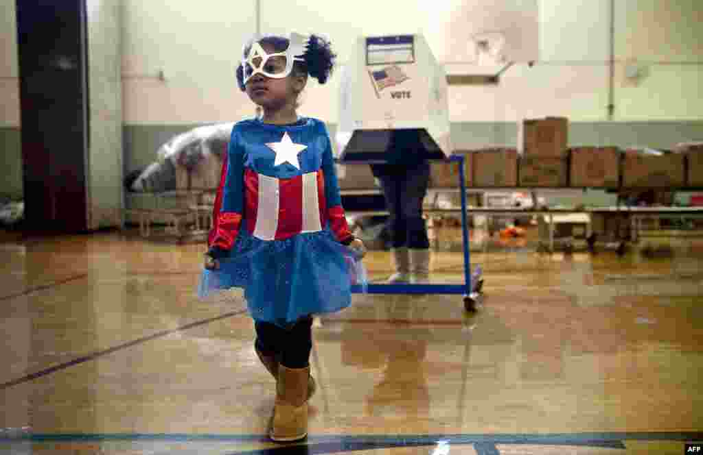 Raena Lamont, 3, wears a Captain America costume at a polling center doubling as a donation site in the Staten Island borough of New York City.