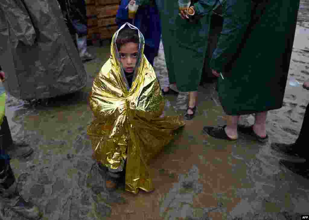 A child wrapped in a survival blanket looks on as migrants queue for hot soup in a makeshift camp at the Greek-Macedonian border, near the Greek village of Idomeni, where thousands of refugees and migrants are stranded by the Balkan border blockade. (AFP/Daniel Mihailescu)