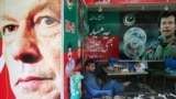A Pakistani vendor sits next to images of Imran Khan at a market in Islamabad on July 27.
