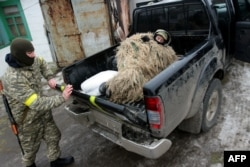A Ukrainian serviceman wearing camouflage lies in a pickup truck as he prepares to take up a position on the front line near the southern city of Mariupol on January 26.