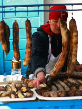 A Kyrgyz vendor sells sausages prepared from horse meat at Bishkek's Osh Bazaar. (file photo)
