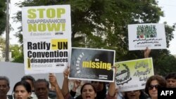 FILE: Pakistani human rights activists carry placards and banners during a protest for missing persons to mark the International Day of the Victims of Enforced Disappearances in Karachi.