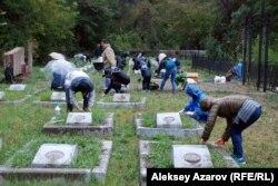 Совет тұтқынында қаза болған отандастары жерленген зират басын тазартып жатқан жапон азаматтары. Алматы, 19 қыркүйек 2015 жыл.