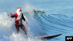 Surfing Santa Michael Pless, 61, catches a wave at Seal Beach, south of Los Angeles on December 24. (AFP/Frederic J. Brown)