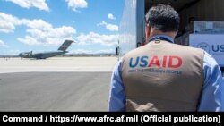 A USAID employee watches a U.S. Air Force plane preparing to deliver coronavirus aid to Russia last year.