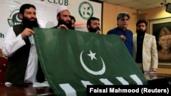 FILE: Saifullah Khalid (2nd L), President of Milli Muslim League (MML) political party, holds a party flag with others during a news conference in Islamabad, August 2017