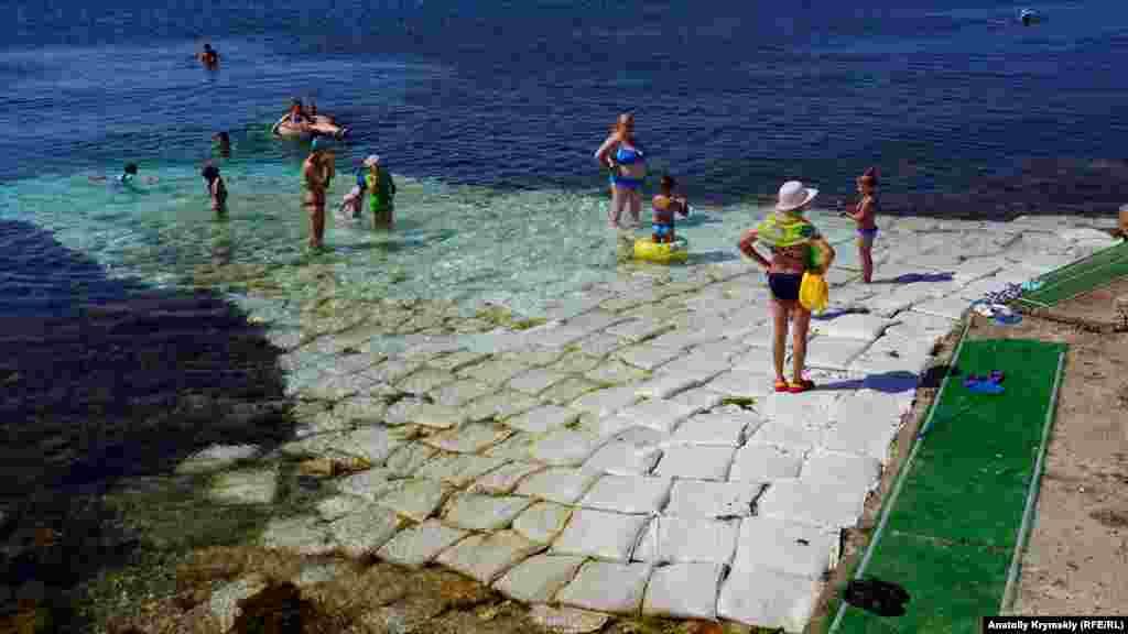 Для удобства отдыхающих каменистое мелководье устелили мешками с мелким щебнем