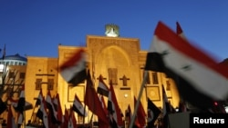 Syrian activists wave flags during a sit-in protest outside the parliament building in Damascus on February 21.