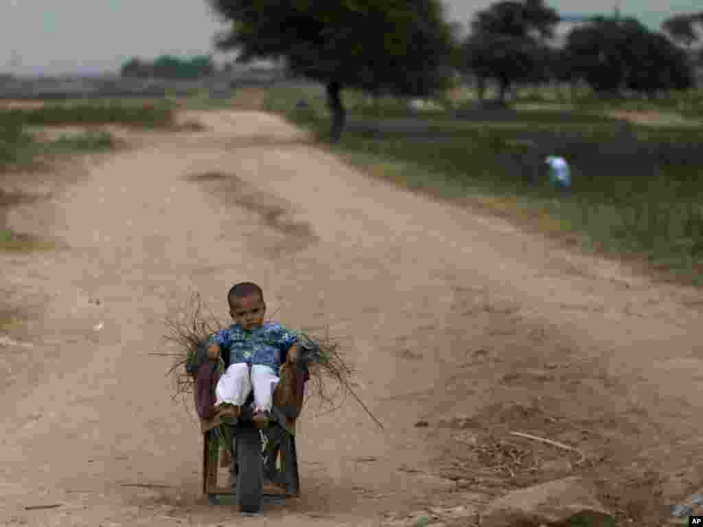 A Pakistani child sits in a wheelbarrow loaded with wood on the outskirts of Islamabad, Pakistan. (Photo by Muhammed Muheisen for AP)