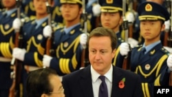 Chinese Prime Minister Wen Jiabao (left) and his British counterpart David Cameron review an honor guard welcoming Cameron to Beijing.