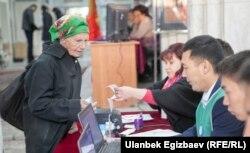 Сайлау бюллетенін алып жатқан сайлаушы. Қырғызстан, Бішкек, 15 қазан 2017 жыл.