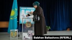 Женщина опускает бюллетень в избирательную урну на участке в Алматы. 20 марта 2016 года.