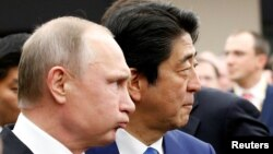Russian President Vladimir Putin (left) with Japanese Prime Minister Shinzo Abe in Tokyo on December 16.