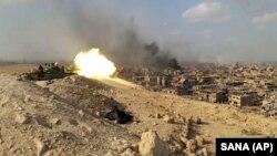 """Танк сирийской армии наносит огонь по предполагаемым позициям боевиков """"Исламского государства"""" в Дейр-эз-Зоре. 2 ноября 2017 года."""