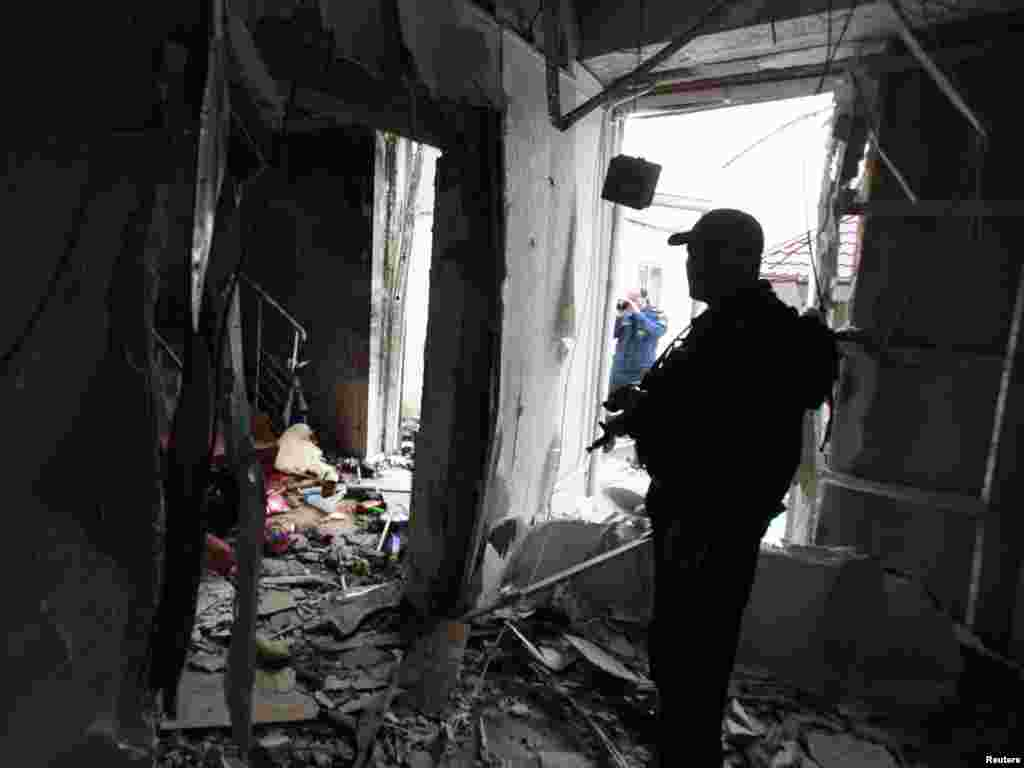 A security officer stands guard inside the damaged parliament building in Grozny, Chechnya, on October 19. Islamist rebels killed at least four people as they tried to seize Chechnya's parliament in a brazen suicide attack. Photo by Kazbek Basayev for Reuters