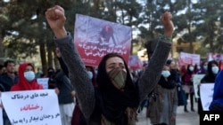 Afghan Solidarity members hold posters and chant slogans as they stage a protest against the stoning of Rukhshana in the capital Kabul in November.