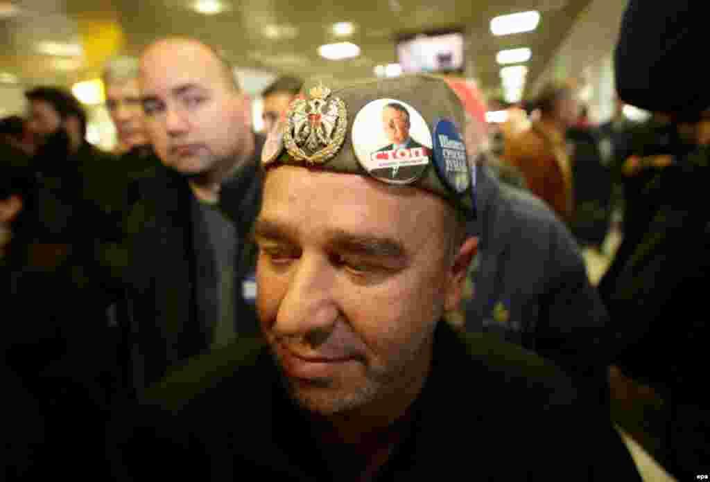 Як тарафдори як раҳбари миллатгарои серб Воислав Сеселҷ дар интизори ӯ дар фурудгоҳи Белград.