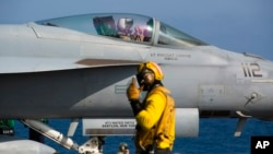 A crew member signals to a pilot in an F/A-18 fighter jet on the deck of the USS Abraham Lincoln aircraft carrier in the Arabian Sea, Monday, June 3, 2019.