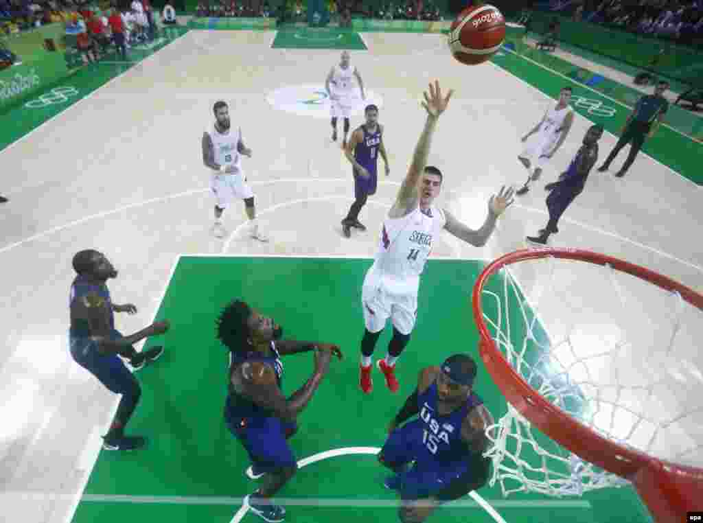 Nikola Jokic of Serbia (center) shoots over DeAndre Jordan of the United States in the men's basketball final. The U.S. team won 96-66.