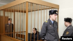 Belarus -- Former opposition campaigner Vasil Parfyankau sits in a cage guarded by the police in a court room in Minsk, 17Feb2011