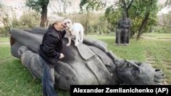 Egy moszkvai férfi a bulldogjával játszik a KGB-t megalapító Feliksz Dzerzsinszkij szobrán egy belvárosi parkban. Moszkva, 1991. augusztus 31.