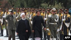 Iranian President Hassan Rohani (left) and Pakistani Prime Minister Imran Khan reviewing an honor guard in Tehran on April 22