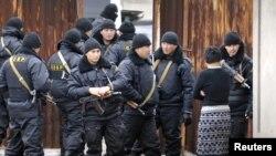 Казак коопсуздук күчтөрү Боролдойдо атышуу болгон үйдүн жанында. 4-декабрь, 2011-жыл.