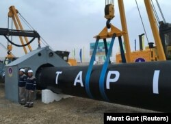 Turkmen workers stand near a gas pipe during the February 23 launching ceremony for construction work on the TAPI pipeline.