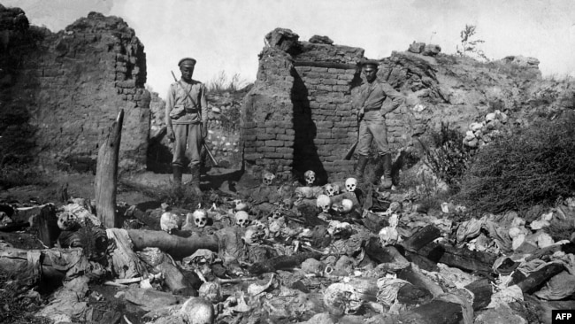 A 1915 photo purportedly shows soldiers standing over the skulls of victims from the Armenian village of Sheyxalan in the Mush Valley, on the Caucasus front during World War I.