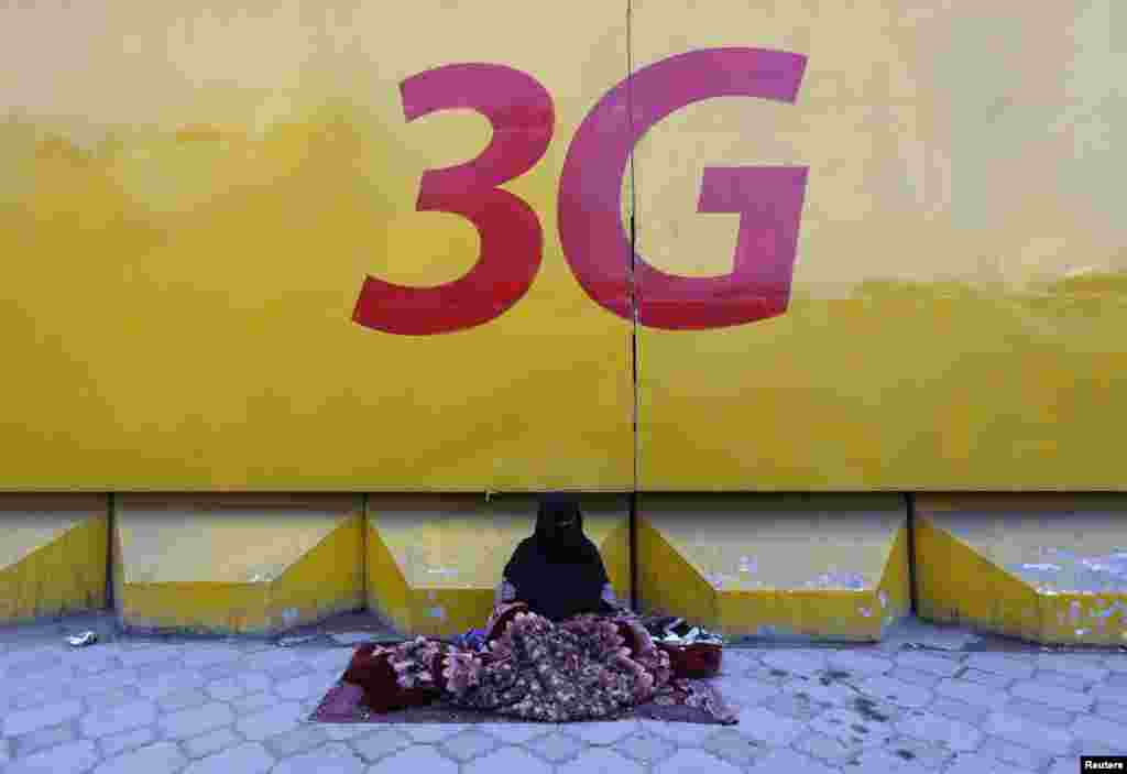 An Afghan woman begs under a 3G logo in Kabul on March 8 (International Women's Day)