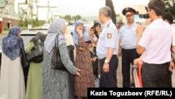 Полицейские не допускают к зданию прокуратуры протестующих жен узбекских беженцев-мусульман. Алматы, 9 июня 2011 года.