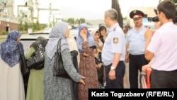 Полицейлер өзбек босқындарының әйелдерін прокуратура ғимаратына жібермей тұр. Алматы, 9 маусым 2011 жыл.