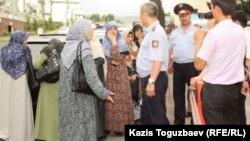 Полицейские не допускают к зданию прокуратуры жен узбекских беженцев-мусульман. Алматы, 9 июня 2011 года.