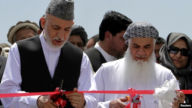President Hamid Karzai (left) inaugurates a power plant north of Kabul in June with Mohammad Ismail Khan, who says he has Karzai's full support.