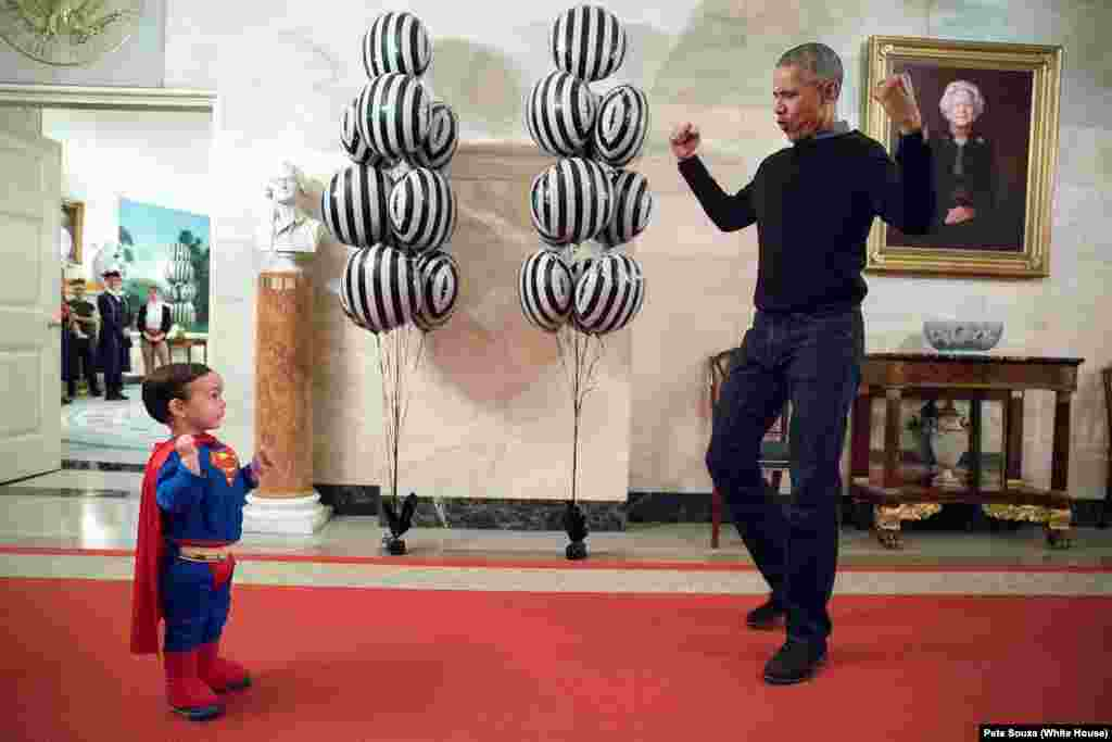 Walker Earnest, the son of Obama's Press Secretary Josh Earnest, flexes his muscles with the president during Halloween trick-or-treating at the White House on October 31, 2016.