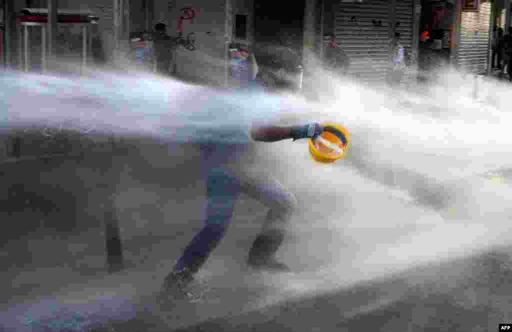 A Turkish protester runs as police used water cannon during clashes on Istiklal Avenue in Istanbul. (AFP/Bulent Kilic)