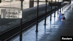 Një grua kalon sot para një stacioni të zbrazët të trenave në Athinë