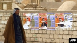 Election posters on a wall at Al-Najaf cemetery in Iraq