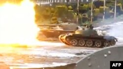 An image grab taken from a video uploaded to YouTube on February 10 purportedly shows a tank firing in the Baba Amro neighborhood in Homs on February 10.