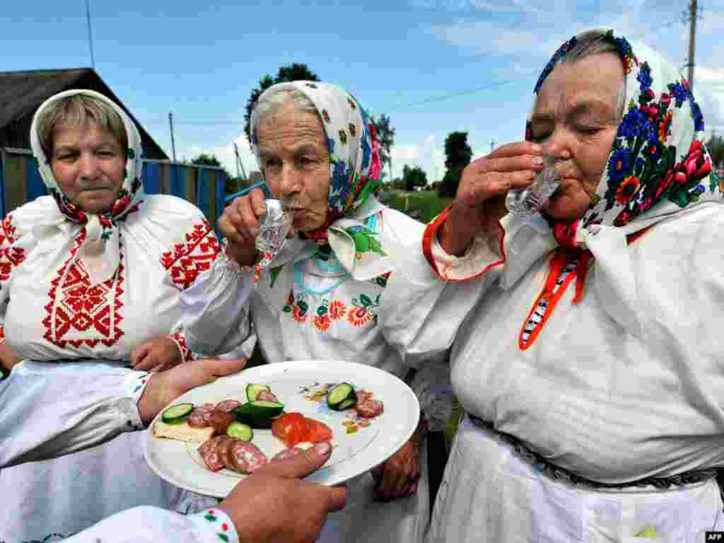 Belarusian women in traditional dress drink vodka in the village of Plastok, south of Minsk, during the Orthodox celebration of Trinity Sunday. Photo by Victor Drachev for AFP