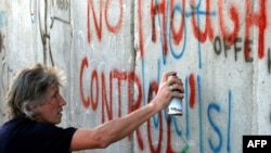 Roger Waters, co-founder of the rock group Pink Floyd, paints graffiti on a visit to Israel.