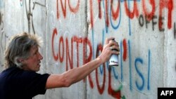 راجر واترز خواننده گروه «پینک فلوید» در حال شعارنویسی بر روی یکی از دیوارهای حائل در کرانه باختری.