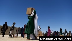 An internally displaced woman carries free aid distributed during the holy month of Ramadan in a refugee camp on the outskirts of Mazar-e Sharif.