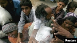 Flood victims scramble for sacks of flour distributed by volunteers in the outskirts of Karachi on August 16.